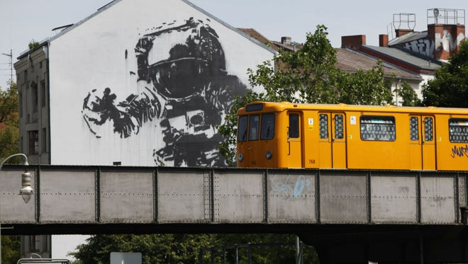 A subway train passes a building featuring a giant street art picture of an astronaut in Berlin's Kreuzberg district on July 12, 2010.