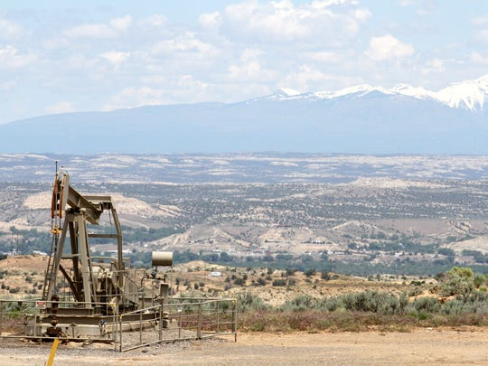 An oil well is seen with the La Plata Mountains in the background May 29 south of Bloomfield on U.S. Highway 550.