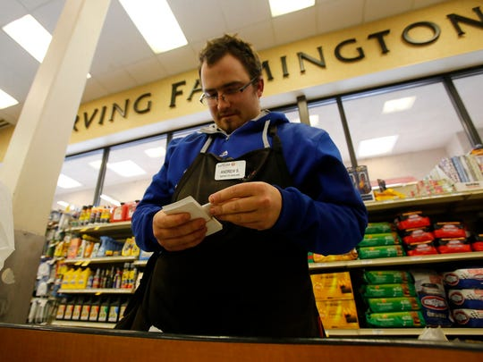Safeway food clerk Drew Schulz sorts through tags Tuesday at Safeway on West Main Street in Farmington.