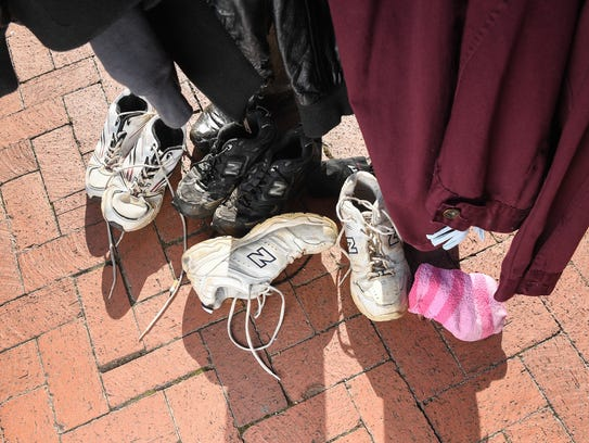 A coat, sweater, shoes and a pair of socks are left