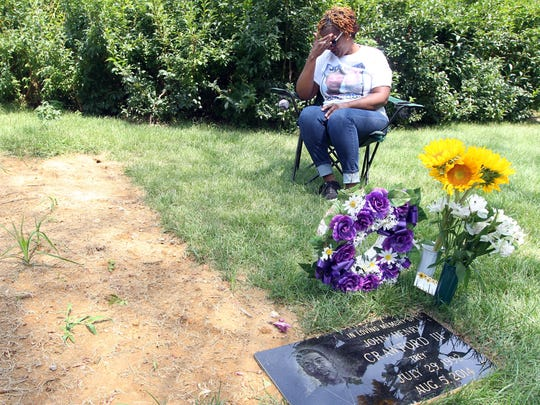 Tressa Sherrod, whose son, John Crawford III, 22, was shot and killed by a Beavercreek police officer while holding an air rifle/pellet gun he picked up from a store shelf  in a Beavercreek Wal-Mart store, visits her son's grave in Spring Grove Cemetery on the one-year anniversary of his death. Sherrod lives in Colerain Township. She sits at the grave at least once a week, sometimes accompanied by her mother, Annie Trimm, of Bond Hill.   Her son lived in Fairfield at the time of his death. A grand jury declined to indict the police officer, Sean Williams, who shot Crawford twice with an assault rifle.