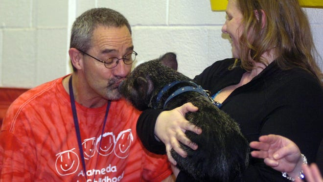 Terry Schneider kisses Dillon the pig.