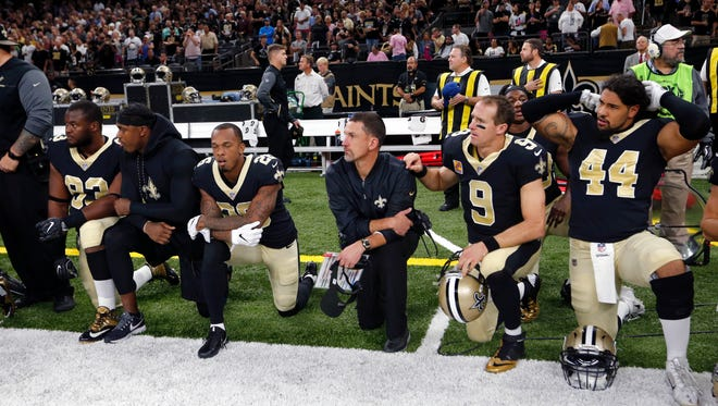 Members of the New Orleans Saints, including QB Drew Brees (9), kneel for a moment of silence for fallen New Orleans Police officer Marcus McNeil before the game against the Lions in New Orleans, Sunday, Oct. 15, 2017. The players then stood for the national anthem.