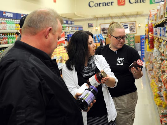 "Jen Bylaw, center, dietetic technician with Coshocton Hospital, shows Steve Hall, of West Lafayette, and Lindsey Childress, of Coshocton, what to look for on nutrition labels Oct. 23 at Baker's IGA in the Downtowner Plaza as part of ""Take Charge of Diabetes,"" a free six-week program hosted by the hospital."