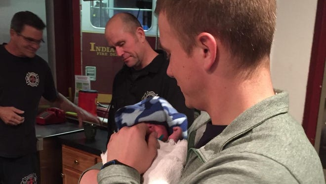 An Indianapolis firefighter holds a newborn that was handed over to IFD Station 30 under Indiana's Safe Haven Law.