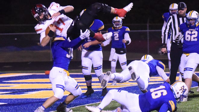Searcy quarterback Mason Schucker attempts to leap over Mountain Home's Riley Peters for a touchdown Friday night at Bomber Stadium.