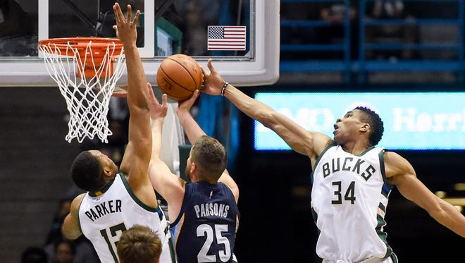 Jabari Parker and Giannis Antetokounmpo of the Bucks block a shot by Grizzlies forward Chandler Parsons in the fourth quarter at the BMO Harris Bradley Center. The Bucks beat the Grizzlies, 106-96.
