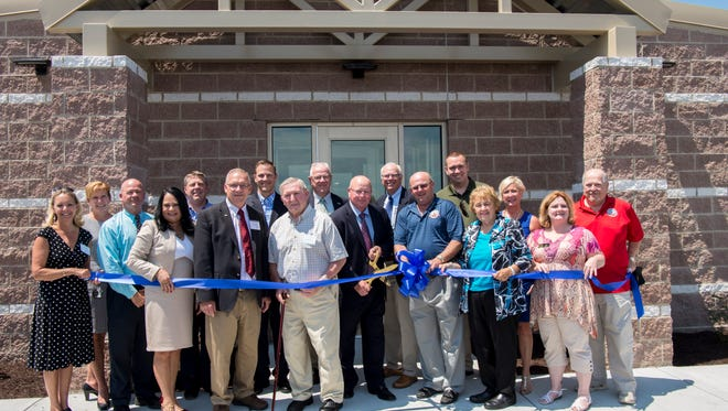 A group of Sharp Energy employees gather around to cut the ribbon on their new headquarters.