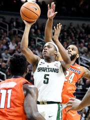 Michigan State's Cassius Winston, center, shoots between Illinois' Greg Eboigbodin, left, and Mark Alstork during the first half on Tuesday, Feb. 20, 2018, at the Breslin Center in East Lansing.