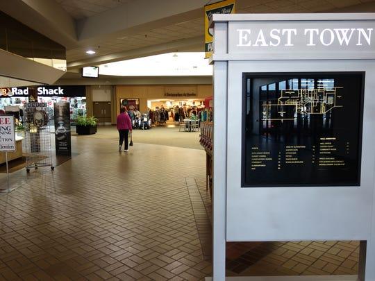 A shopper walks through East Town Mall in Green Bay.