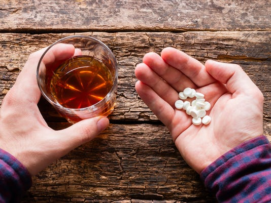 man holding a glass of alcohol and pills
