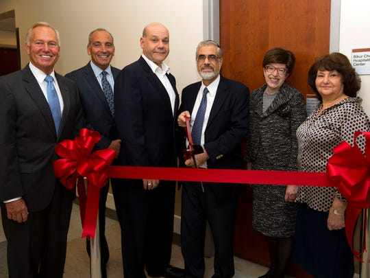 Robert Wood Johnson University Hospital hosted a ribbon cutting on Sept. 7 to unveil a new hospitality room created through a partnership with Bikur Cholim of Raritan Valley. From left: New Brunswick Mayor Jim Cahill; RWJ President and CEO Michael Antoniades; Robert Wood Johnson University Hospital Board of Directors President Jack Morris; Rabbi David Bassous, spiritual leader of Congregation Etz Ahaim in Highland Park; Rahel Baruh, representing Bikur Cholim of Raritan Valley; and Gloria Morris. RWJUH is at 1 Robert Wood Johnson Place in New Brunswick.