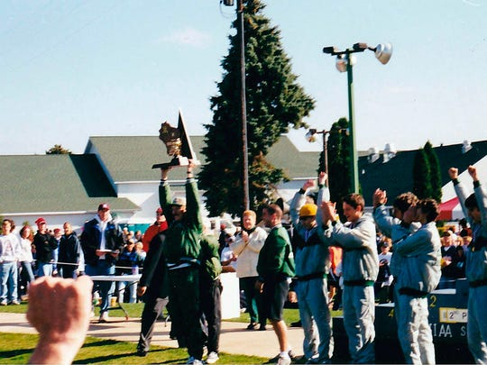 West Allis Hale cross country coach Ron Kurtz raises the 2000 WIAA Division 1 state cross country championship trophy.