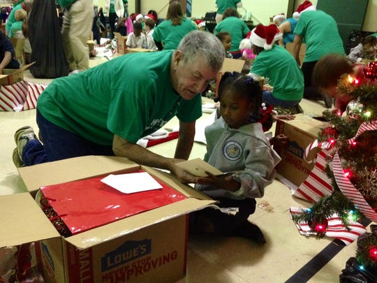 Calvary Baptist member and volunteer John Cain helps kindergartener Ja'Mirah Johnson read a Christmas card found in her gift from the church. Volunteers delivered gifts to every student at Julius Patrick Elementary in Alexandria with a Christmas party on Tuesday.
