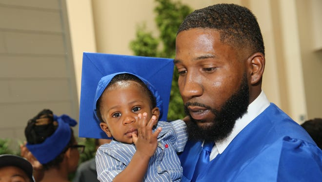 Xavier Henderson holds his 1-year-old after the Metro Action Commission graduation ceremony.