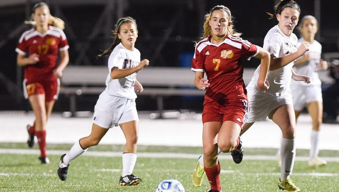 Mater Dei's Sunny Lehman (center) races to the ball in an attempt to shoot during the Wildcats' semistate championship game against Lawrenceburg, October 24, 2015.