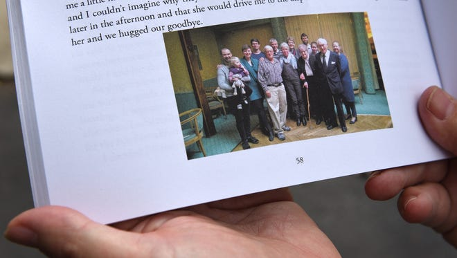 Former South Lyon Mayor Wallace shows a photo from his book taken of him in Denmark with the family of Svenv Hill-Matson - the man who attempted to save him from drowning in St. Croix.