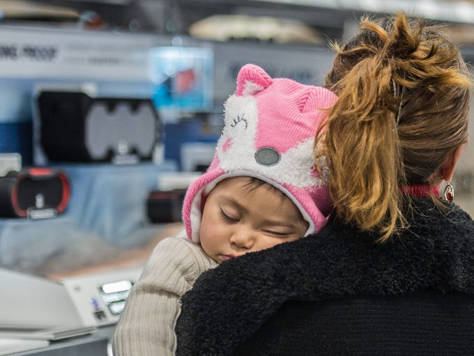 A baby sleeps on her mother's shoulder at Best Buy
