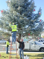 City employees hang ornaments made by Yerington Elementary School students on a tree outside city hall.