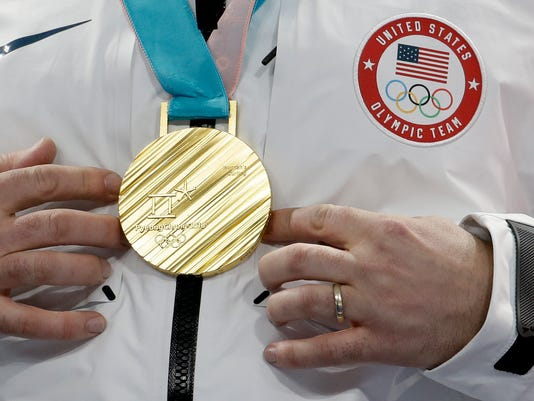 United States's skip John Shuster puts his hands near his gold medal after winning the men's final curling match against Sweden at the 2018 Winter Olympics in Gangneung, South Korea, Saturday, Feb. 24, 2018. (AP Photo/Natacha Pisarenko)