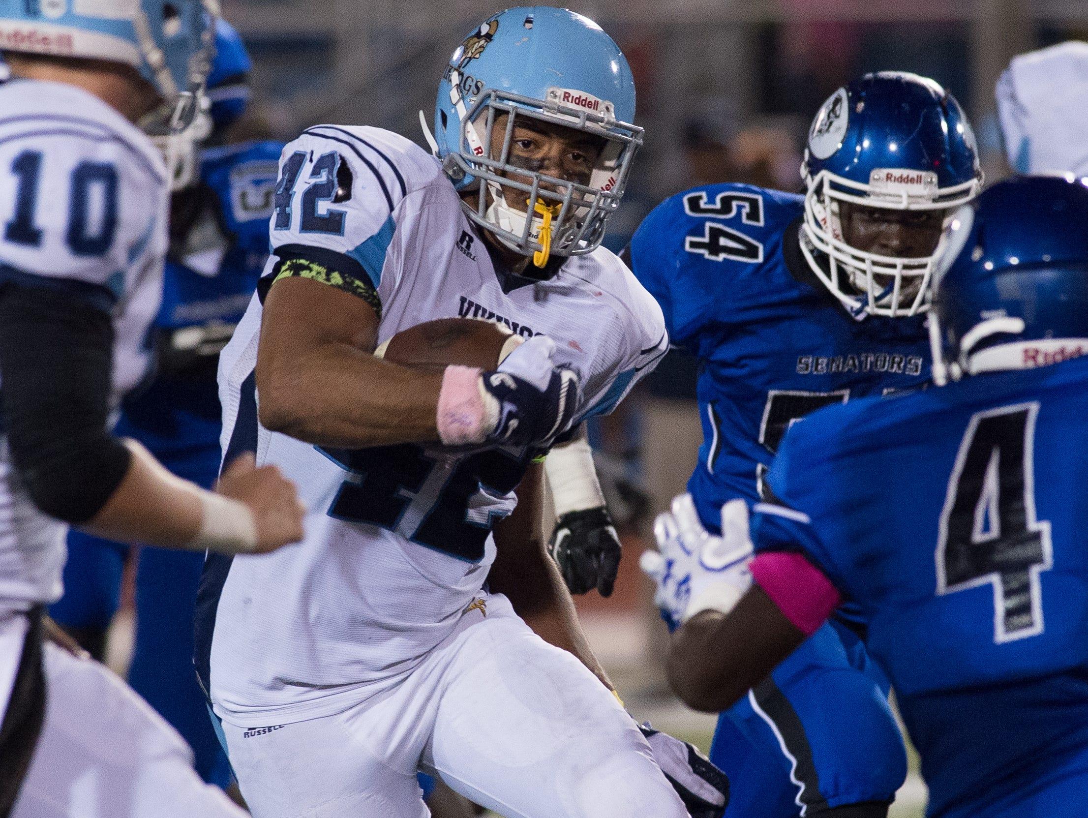 Cape Henlopen's Kolbi Wright (42) runs the ball through Dover's defense.