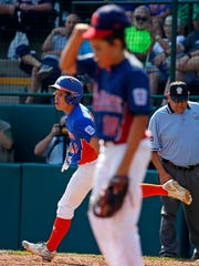 Grosse Pointe, Mich.'s Joey Radanzzo, rear, rounds first behind Jackson, N.J., pitcher Chris Andrews (10) after hitting a solo-home during the second inning of an elimination baseball game in United States pool play at the Little League World Series tournament in South Williamsport, Pa., Saturday, Aug. 19, 2017.