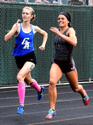 Karlie Zumbro, right, tries to outrun Gallipolis Gallia Academy's Madi Oiler in the finals of the 300 hurdles during last season's Division II regional track meet at Athens High School. Zumbro signed her letter of intent to compete for Ball State University on Wednesday.