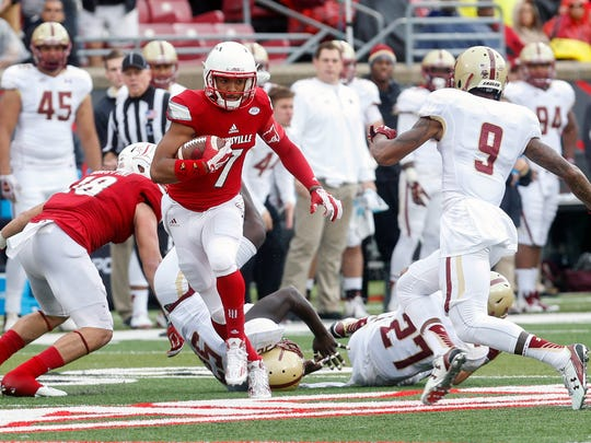 Louisville's Reggie Bonnafon gets past a couple of defenders and gets ready to make contact with Boston College's John Johnson. 