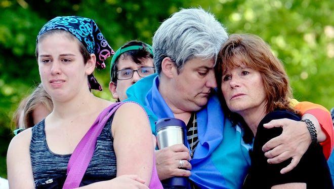 Aidan Wood, left, her mom, Lisa Laughman and Karen Pace console each other at a vigil at the Capitol for the mass shootings in Orlando on Sunday, June 12, 2016. The Lansing Association for Human Rights organized the event.