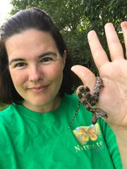 Tanee Janusz poses with a two-headed Western rat snake. The snake was found in a friend's yard.