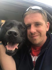 Veteran Ryan Koch smiles with his service dog Stanley,