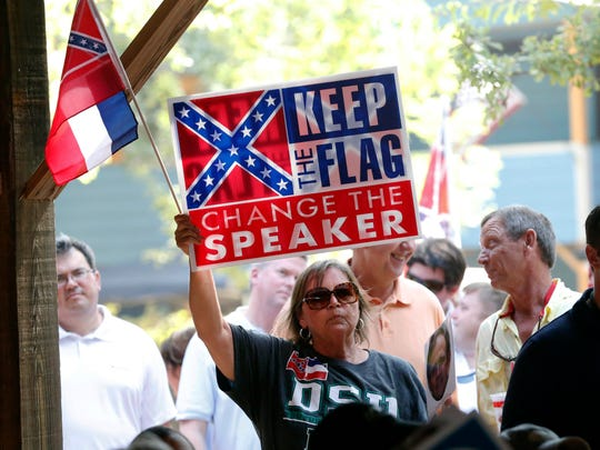 A current flag supporter waves her protest sign and a small Mississippi state flag at the Neshoba County Fair in Philadelphia, Miss., Thursday, July 30, 2015. A small number of protestors made their feelings known as they waves flags and signs in peaceful protest during an address by the Speaker of the House Philip Gunn, who has called for the flag's replacement. The fair is a traditional gathering place for politicians, area residents, business leaders, voters and families. (AP Photo/Rogelio V. Solis)