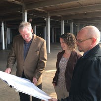Wisconsin Redevelopment partners Bob Lemke, left, and Todd Hutchison, right, review plans intended to turn former Mirro Plant 3 into 40 downtown apartments. They will be aided by Impact Seven real estate development director Rachel Kennedy, center.