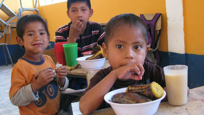 Children in a Guatemalan grade school enjoy their school meal (often their only meal in the day), consisting of tortilla, frijoles molidos and a platano, as well as a drink of atol, a kind of porridge made of a corn and soy blend.