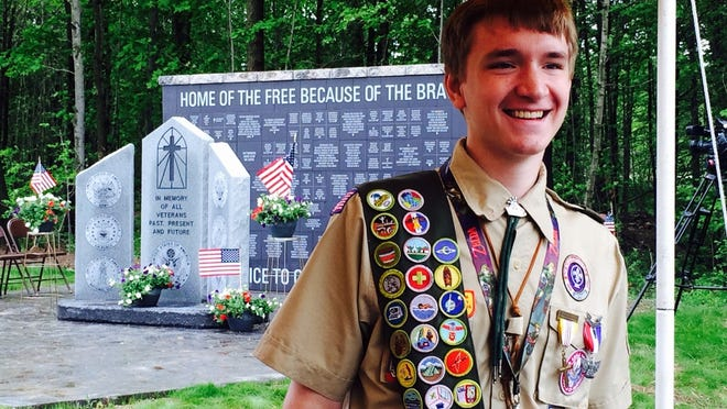 Eagle Scout Daniel Weller visits with his scoutmaster on Monday in Hatley after the dedication of a monument to veterans (behind him) that he spearheaded for his Eagle project.