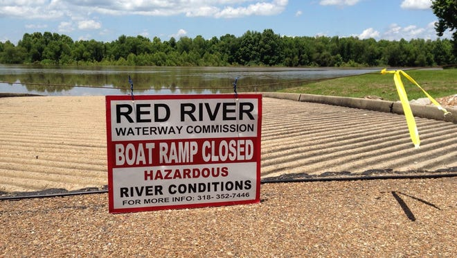 A sign tells boaters that the public launch at the Boyce Recreation Area is closed because of conditions on the Red River. The river was to reach flood stage Monday evening and continue rising to about 38 feet over the next week.