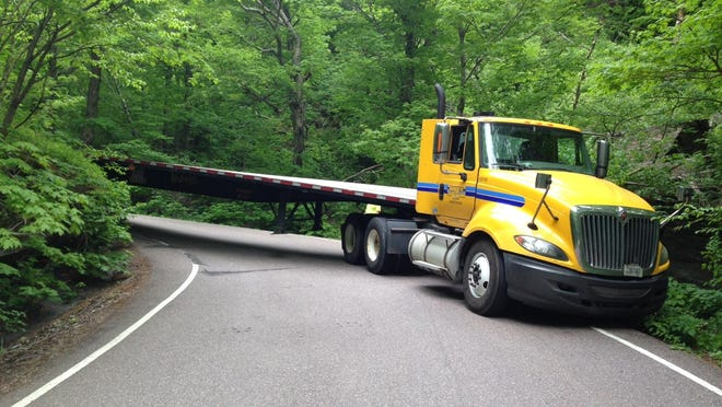 A tractor trailer truck blocks Vermont 108 in Smugglers Notch after it became wedged between boulders on a sharp corner in on Vermont 108, which goes from Cambridge to Stowe.