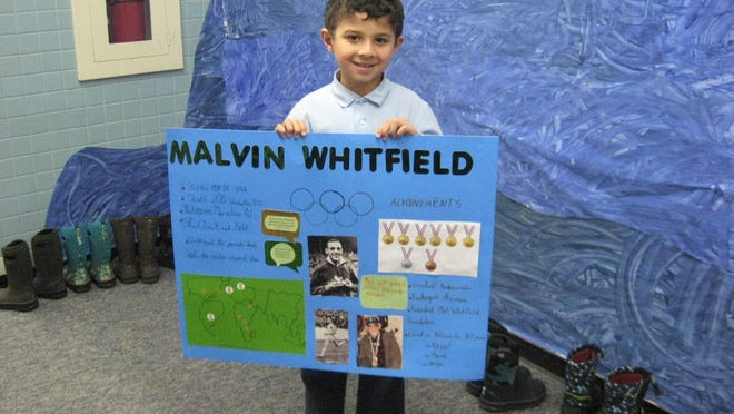 One of the Mater Christi first-graders holding his poster of Olympian track runner Malvin Whitfield. The youngster chose Malvin Whitfield because he wants to become a successful track runner, too.
