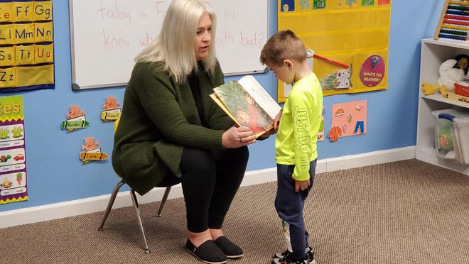 Teacher Karen Colfax helps Xander Brina, 4, read from a book at The Kid's Place in Slate Hill. Many local child care centers have seen a dramatic drop in enrollment due to the coronavirus crisis.