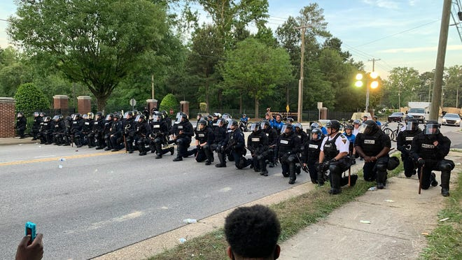 Fayetteville police officers in riot gear take a knee on June 1, 2020, in Fayetteville during a protest of the death of a black man in Minneapolis in the custody of white police officers.