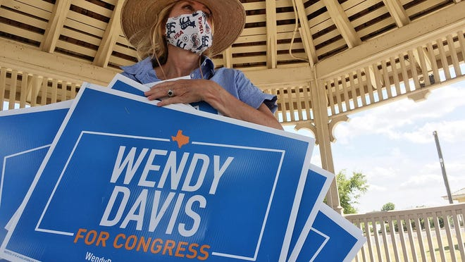 Democratic U.S. House candidate Wendy Davis grabs the remaining yard signs after handing them out to supporters at the Gazebo in downtown Buda on Aug. 30.