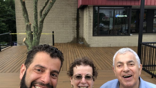 The Gjinis family, proprietors of The Specialty Bar and Grill in Holden: from left, Vasilios, known as 'Bill', his mother, Aphrodite, and father, Ilias. The trio are standing on the business' new patio.