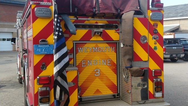 """HIngham's """"thin blue line"""" flag, which was removed from the town's fire truck,"""" was placed on Engine 3 of the Weymouth Fire Department Monday morning."""