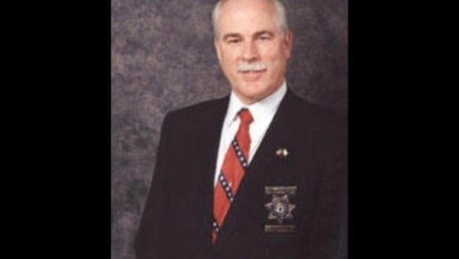 Critics claim this tie, worn by the sheriff in a photo from 2003, is similar to ties sold on a website that sells Confederate flag themed items.