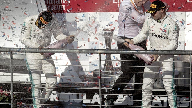 Mercedes driver Lewis Hamilton, left, sprays teammate Valtteri Bottas with champagne as they celebrate their titles following the 2019 Formula One U.S. Grand Prix at Circuit of the Americas. The 2021 Formula One race is scheduled for Oct. 24 according to a calendar released today by race officials.