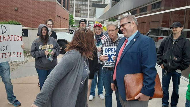 State Rep. Darren Bailey, R-Xenia, talks with protesters outside the Bank of Springfield Center arena May 20. A judge on Thursday, July 2, 2020, ruled in favor of Bailey, who filed a lawsuit challenging COVID-19-related executive orders issued by Gov. JB Pritkzer.