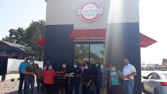 Scooter's Coffee employee Esteban Marboeuf cuts the ribbon to officially open the second Scooter's location in Dodge City.