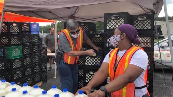 Volunteers hand out milk at a recent Manna House food drive.