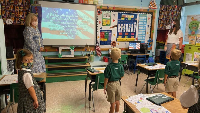 Miss Latimer and Mrs. Parrot's kindergarteners say the pledge of allegiance along with the schoolwide broadcast on the screen.