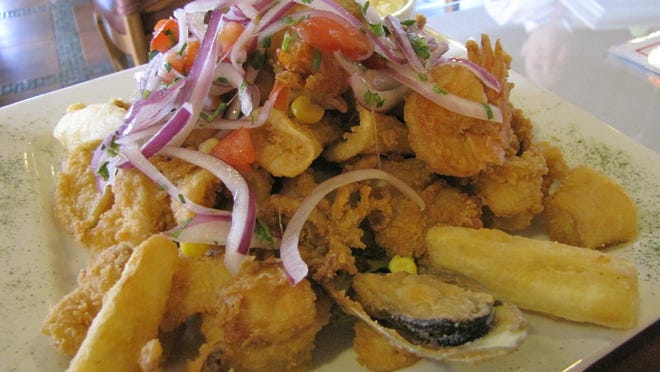The jalea mixta from El Patio features a mound of fried seafood and yucca laced with a tangy salad of red onions and vegetables.
